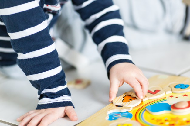 child-is-playing-with-wooden-clock-puzzle_181624-10841.jpg